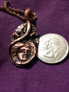 QUESTIONS. This copper pendant features the face of the Roman goddess Diana. Three frogs stare inquisitively at her, while a vine wraps around the entire scene. What are the frogs asking? It is not to be revealed.