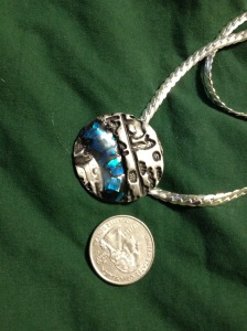 BLUE NILE. This pendant is made of fine silver, with a 'Nile' of acrylic, containing chips of paua shell, running through it. The heiroglyphics don't really say anything -- sorry. The coin is for scale.