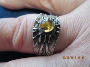 EYE OF THE FOREST. A citrine stone sits in the middle of this silver ring. The silver ridges represent the tangled roots of ancient trees.